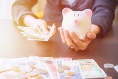 Prosiątko bank w ręce z gotówka stosem Zdjęcia Stock