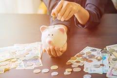 Prosiątko bank w ręce z gotówka stosem Zdjęcie Stock