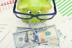 Prosiątko bank w szkłach nad pieniężnymi mapami z 100 dolarami banknotów przed nim Zdjęcia Royalty Free