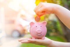 Prosiątko bank z ręki oszczędzania pieniądze obrazy stock