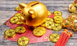 Prosiątko bank z złotymi monetami, czerwieni kopertami i chińskim ornamentem na drewnianym stole, obraz stock