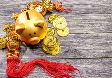 Prosiątko bank z złotymi monetami i chiński ornament na drewnianym stole obraz stock