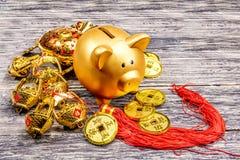 Prosiątko bank z złotymi monetami i chiński ornament na drewnianym stole fotografia stock