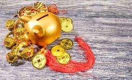 Prosiątko bank z złotymi monetami i chiński ornament na drewnianym stole zdjęcia stock