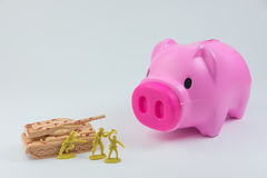 Prosiątko bank z zbiornikiem i żołnierze w pojęciu łamanie deponujemy pieniądze fo fotografia stock