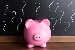 Prosiątko bank z znakiem zapytania na czerni desce Obraz Stock