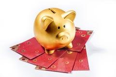 Prosiątko banka pozycja na czerwonych kopertach obraz stock
