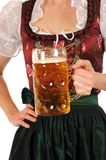 Prosit. A young woman in Bavarian Dirndl is holding a stein with one liter beer Royalty Free Stock Images
