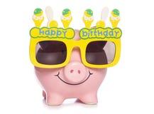 Prosiątko bank jest ubranym urodzinowych szkła Zdjęcia Royalty Free