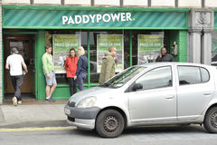 Prospect Hill, Galway, Ireland June 2017, Paddy Power betting ho. Use, man with sportive clothes entering , young people smoking outside Stock Photo