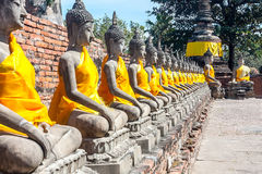 The prospect of a number of statues of Buddha, Thailand. The prospect of a number of statues of seated Buddha, Thailand. Statues in yellow festive decoration Royalty Free Stock Photography