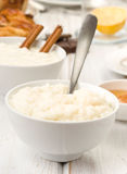 Prospect of overflowing bowls of rice pudding, on wood Stock Photo