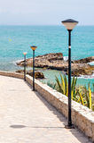 The prospect of the street down to the sea. Valencia. Spain. The street paved with stone, lights. Rocks and plants on the Mediterranean coast. Sunny day and a Royalty Free Stock Photos