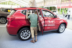 Prospective buyer inspecting a Haval brand Chinese automobile SUV on display at Dongguan car exhibition Stock Image