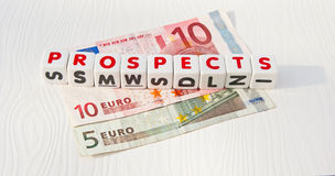 Prospects for the Euro. Text 'prospects' in red uppercase letters inscribed on small white cubes placed upon five and ten Euro notes royalty free stock photos