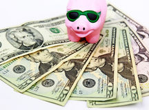 Prosperity. Pink piggy bank wearing sunglasses smiling stepping on dollar bills. A concept of prosperity royalty free stock photo