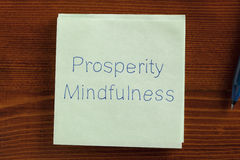 Prosperity Mindfulness written on a note. Top view of Prosperity Mindfulness written note on the wooden desk with pen aside stock images