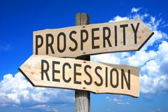 Prosperity, recession - wooden signpost. Wooden signpost with two arrows `prosperity` and `recession` - sky with clouds in a background Stock Photography