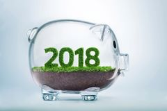 2018 prosperity year concept. 2018 is a good year for business. Grass growing in the shape of year 2108, inside a transparent piggy bank Stock Image