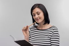 Prosperous businesswoman making some notes in black notebook. Prosperous businesswoman. Image without face retouching with prosperous businesswoman making some stock photography