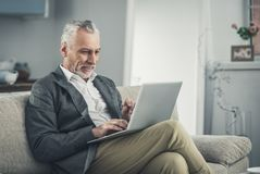 Prosperous experienced businessman working on laptop. Experienced businessman. Prosperous experienced handsome businessman wearing stylish grey jacket working on stock photos
