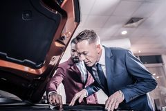 Prosperous man wearing hand watch looking into opened front trunk royalty free stock photo