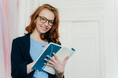Free Prosperous Satisfied Businesswoman In Elegant Clothes Writes In Diary, Has Glad Expression, Wears Spectacles, Makes List Of Plans Royalty Free Stock Photography - 146823077