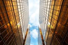 Prospettiva ascendente dei grattacieli contemporanei simmetrici, con cielo blu e le nuvole bianche Immagine Stock