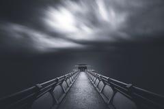 Prospettiva della strada verso una torre con muoversi della nuvola soffiato da forte vento Fotografie Stock Libere da Diritti