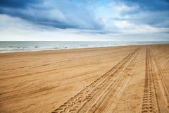 Prospettiva delle piste del pneumatico sulla spiaggia sabbiosa Fotografia Stock