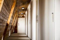 Prospettiva di un corridoio con le pareti di legno in un hotel o in un dormitorio Fotografia Stock Libera da Diritti