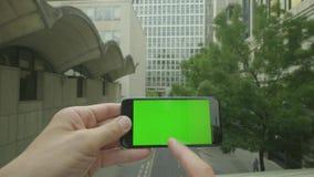 Prospettiva personale di un uomo che per mezzo di uno smartphone dello Verde-schermo fuori dell'ufficio stock footage