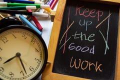 Prossiga o bom trabalho em escrito à mão colorido da frase no quadro, no despertador com motivação e nos conceitos da educação imagens de stock royalty free