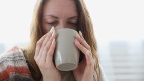 Prosta kobieta pije herbaty zawijającej w ciepłej woolen koc zbiory