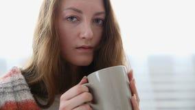 Prosta kobieta pije herbaty zawijającej w ciepłej woolen koc zdjęcie wideo