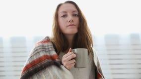 Prosta kobieta pije herbaty zawijającej w ciepłej woolen koc zbiory wideo