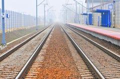 Prosta kolej przewozi samochodem w mgle z stacyjnym, platformą na stronie/ Obraz Royalty Free