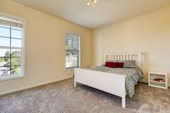 Prosta sypialnia z miękkimi brzoskwini ścianami na piętrze, szary dywan Zdjęcie Stock