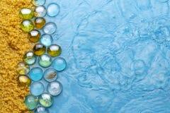 Prostacki piasek z przejrzystymi kamieniami na tle błękita jasnego woda poj?cia t?a ramy piasek seashells lato imitacja plaża fotografia stock
