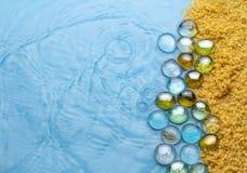 Prostacki piasek z przejrzystymi kamieniami na tle błękita jasnego woda poj?cia t?a ramy piasek seashells lato imitacja plaża zdjęcie royalty free