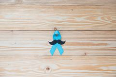 Prostate Cancer Awareness, hand holding light Blue Ribbon with mustache on wooden background. Prostate Cancer Awareness, light Blue Ribbon with mustache on royalty free stock photography