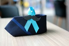Prostate Cancer Awareness. Light Blue Ribbon with mustache and necktie for supporting people living and illness. Men Healthcare and World cancer day concept stock image