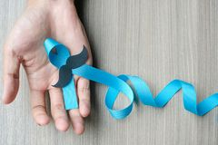Prostate Cancer Awareness. Man hand holding light Blue Ribbon with mustache for supporting people living and illness. Men Healthcare and World cancer day stock image