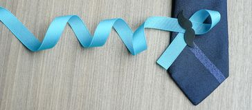 Prostate Cancer Awareness. Light Blue Ribbon with mustache and necktie for supporting people living and illness. Men Healthcare and World cancer day concept royalty free stock photo
