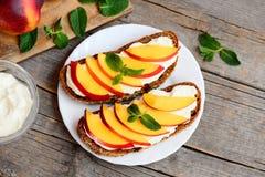 Proste kanapki z kremowym serem, świeżymi nektarynami i mennicą, na talerzu i na rocznika drewnianym stole Bezmięsny lunch Zdjęcia Royalty Free