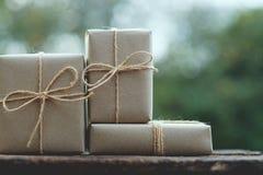 Prostego eco prezenta pudełek pakunku życzliwy opakunek z brązu papierem na drewnianym stole z ogrodowym tłem, zieleni teraźniejs obrazy stock