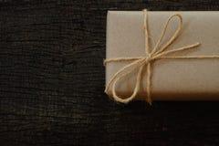 Prostego eco prezenta pudełek pakunku życzliwy opakunek z brązu papierem w starym drewnianym stołowym tle, zieleni teraźniejszy p zdjęcie royalty free