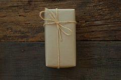 Prostego eco prezenta pudełek pakunku życzliwy opakunek z brązu papierem w starym drewnianym stołowym tle, zieleni teraźniejszy p zdjęcia stock