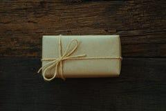 Prostego eco prezenta pudełek pakunku życzliwy opakunek z brązu papierem w starym drewnianym stołowym tle, zieleni teraźniejszy p obrazy royalty free