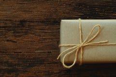 Prostego eco prezenta pudełek pakunku życzliwy opakunek z brązu papierem w starym drewnianym stołowym tle, zieleni teraźniejszy p zdjęcia royalty free
